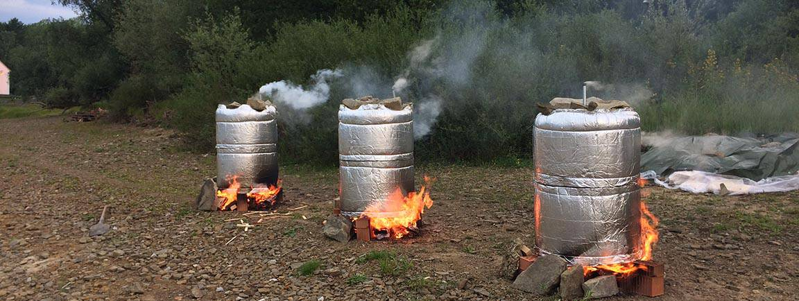 3 Fässer zum Köhlern aus denen Rauch aufsteigt